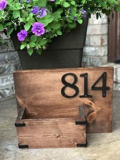 Give your home curb appeal with this simple step by step tutorial on how to create your own DIY house number sign. Change out the flowers in the planter for any season, this wooden house number sign will bring curb appeal to your home. Garden Shelves, House Numbers, Number Signs For House, Diy Hanging, Diy Planters, Diy Signs, Solar Lights, Wooden Diy, Curb Appeal