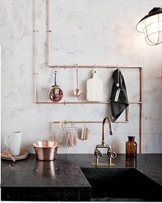 Hang kitchen utensils in an easy to reach spot like your beautiful copper pipes via awelltraveledwoman.