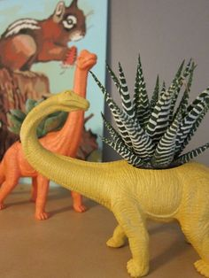 DINO PLANTERS! recycle old dinosaur toys cut a circle out and plant succulents