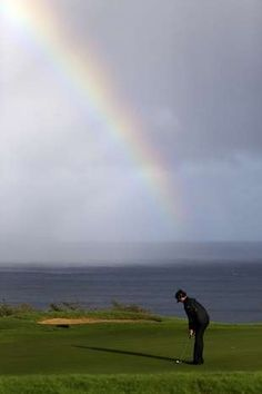 Bubba Watson putts in view of a rainbow behind on the 13th hole during the first round at the Tournament of Champions PGA golf tournament, Monday, Jan. 7, 2013, in Kapalua, Hawaii.