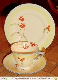 Doulton deco: unnamed tea trio, 1930s. Stylised orange flowers and green leaves offset by yellow banded design and blue highlights and trim.