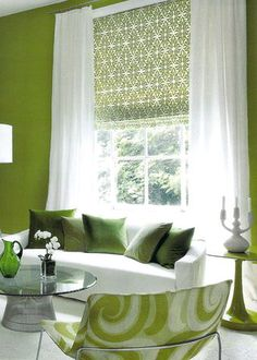 Chartreuse green patterned roman shades under sheer white draperies.