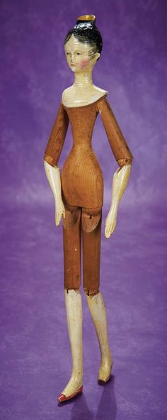 "Early and Large Grodnertal Wooden Doll with Yellow Tuck Comb 18"" (46 cm.) All-wooden doll has one-piece head and torso,heart-shaped face,very elongated throat and shapely torso,sculpted yellow tuck comb at her crown and painted black hair with shaded stippling framing the forehead and little spit curls in front of each ear,outlined painted brown eyes,fringed brows,closed mouth,blushed cheeks,dowel-jointing at shoulders,elbows,hips and knees. Grodnertal,circa 1820."