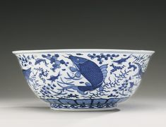 A RARE LARGE BLUE AND WHITE 'FISH' BOWL WANLI MARK AND PERIOD the deep rounded sides rising to an everted rim, the exterior painted with mackerel, white fish, carp and freshwater perch amongst smaller fish and various aquatic weeds, above a band of lappets encircling the base, the interior with a pair of cranes in flight among clouds within a medallion enclosed by a cloud-collar border, and a similar frieze around the rim, six-character mark in underglaze blue within double circles
