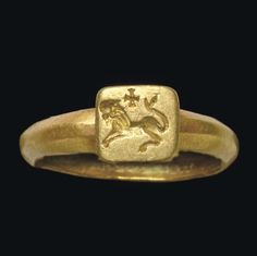 A BYZANTINE GOLD FINGER RING   CIRCA 4TH-5TH CENTURY A.D.   The plain hoop bevelled on the exterior, concave on the interior, with an inverted, truncated pyramidal bezel engraved with a lion leaping in profile to the left, its tail raised, a cross above