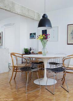 Sala de jantar integrada com mesa Saarinen e cadeiras Thonet e Bertoia.