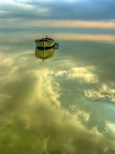 A boat floating on a calm mirror of water.
