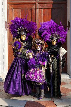 Three people in purple at Carnevale in Venice.