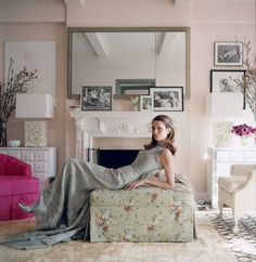 Plum Sykes, in a gray-blue Rochas dress in her sitting room. She had it painted with Pink Ground from Farrow & Ball on the advice of her friend decorator Celerie Kemble. Upholstered chairs and ottoman by Venfield. Flower-filled Perspex lamps by Sasha Sykes.