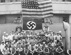 Crewmembers of the USS Omaha pose with a captured Nazi flag after boarding the…