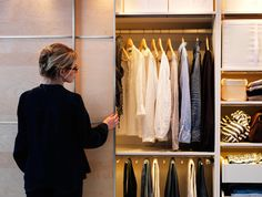 Woman opening a sliding door and looking inside a wardrobe.