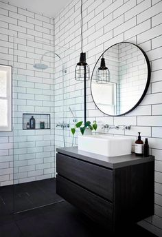 Bathroom White subway tiles are laid horizontally in this smaller bathroom, with the same large format black tiles on the floor. A circular mirror sits above a white basin and black timber vanity, with an industrial-style pendant lamp hangs above. Bad Inspiration, Bathroom Inspiration, Bathroom Renos, Bathroom Renovations, Basement Bathroom, Master Bathroom, Bathroom Design Small, Bathroom Interior Design, Interior Paint