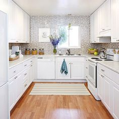 Small, but mighty, this white kitchen is all about function. The U-shape layout is practical, while the glass tile backsplash adds pretty to this hardworking space.
