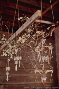 """vintage hanging ladder and shining """"chandelier"""" offer a quirky elegant/rustic element to barn wood decor, This photo is from Elizabethannedesigns and is part of a blog entry about an elegant/rustic wedding. For your rustic decor needs, see us at www.braunfarmtables.com"""