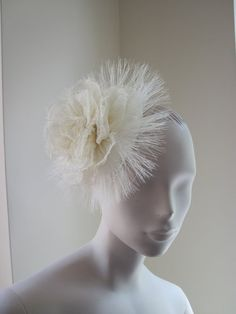 A beautiful cocktail hat in ivory sinamay. The base is handblocked ivory sinamay in a mini beret shape. Decorated with a frayed sinamay rose on top of frayed crin A beautiful statement piece. The hat is held securely in place with a hat elastic which is worn under the hair in the back.  My high quality cocktail hats are made with great care and attention using traditional millinery techniques. They will come in their own hat box for storage, and will be packed securely in sturdy boxes for…