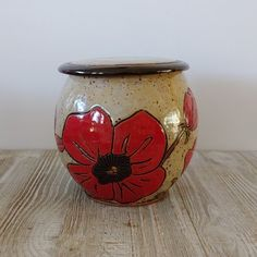 hand carved and hand painted ceramic cremation urn with a series of red poppy flowers going completely around the urn.