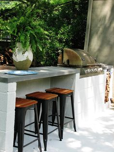A cinder-block bar can stand the elements. And with a grill like that you'll never go back inside.