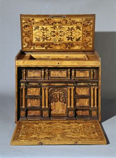 Writing Cabinet, c. 1560. Augsburg. 51 x 64 x 34,5 cm. Spruce, boxwood, carved, marquetry in various woods, partly stained. The colorful intarsias of ruins are typical of Augsburg chests from the 2nd half of the 16th century. The inside is opulently decorated, including small reliefs on the fronts of the drawers. Whether it is a portable writing cabinet, or a small cabinet already being used to contain collections of curiosities, is still open to debate. - Germanisches Nationalmuseum…