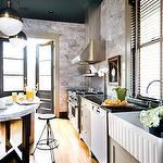 kitchens - gray kitchen cabinets honed black granite countertops oval kitchen island marble countertop industrial stools ribbed farmhouse sink polished nickel goose neck faucet marble backsplash Thomas O'Brien Hicks Pendant
