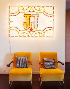 "Neon ""JJ"" sign above small seating area"