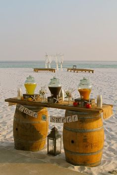 Rustic Beach Wedding Arbor and Farmhouse benches Beach Wedding Ceremony in the background with Barrel Bar Cooling Station set-up featuring Iced Tea, Lemonade, and Vigin Peach Bellini