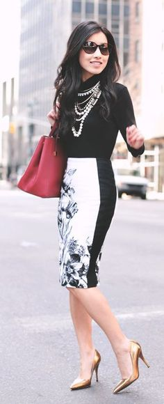 Gorgeous black blouse with black & white stylish plan skirt and dark maroon leather hand bag and golden high heels pumps