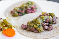 "Carne asada or ""roasted meat"" is grilled beef marinated in lime juice, garlic cilantro and spices. Learn how to make carne asada tacos with this recipe."