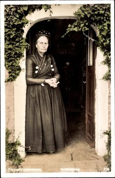Ansichtskarte / Postkarte Ältere Frau in Friesischer Landestracht, Nordfriesland, Hauseingang #Halligen