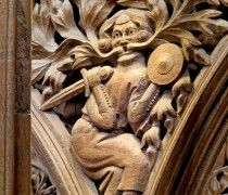 A Green Man with a sword and a shield spews foliage.  Photo by John Crook. One of the greenman sculptures in the stalls at Winchester Cathedral, Winchester, Hampshire, England