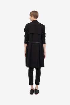 COTTON COAT Shorthaired model wearing a black cotton coat with a black clip belt and sneakers. Design: Lucie Kutálková / LEEDA