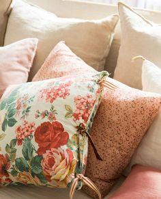 00361561b. Detalle de cojines de sofá en tonos rosas y uno con estampado floral