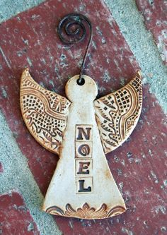 OOAK Rustic Stoneware Angel Ornament this slab is a pendant, the color is white, and has wings, it looks like a angel, and the texture on the wings makes them more like wings.