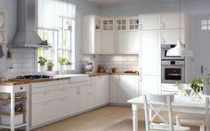 Eine traditionelle Küche mit BODBYN Fronten und BODBYN Vitrinentüren in Elfenbeinweiß, KARLBY Arbeitsplatte in Eiche und integrierten Elektrogeräten