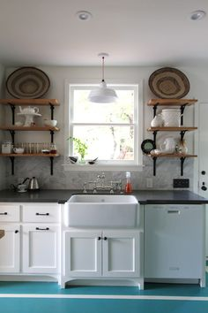 """Grey counter top is Ceasarstone in """"concrete."""" Pendant light above the sink is Barn Light Electric. 
