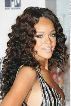 What a gorgeous head of hair. Rihanna's hair is long and completely curled. She has a part down the middle which separates her hair evenly at the sides. Her hair falls nicely down her back and onto her shoulders. This hairstyle frames her face in beautifully. Rihanna's hair is all cut long.The hair colour is a rich dark chocolate brown.