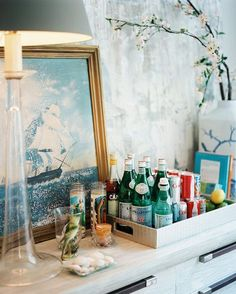 Bar essentials on a tray and a framed nautical artwork on a wooden dining sideboard.