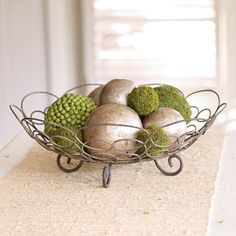 "$25 Looping ironwork with a chalk-brown finish hits just the right note for displaying moss balls or unpeeled fruit. Want an inside tip? This decorative piece is a perfect fit for our Mediterranean Sage Bowl. (15 1/4"" x 5"" tall)"