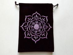 This hand embroidered, unlined black velvet pouch is decorated with a lovely Lotus Flower. The Lotus Flower represents divine beauty and purity, while the unfolding of its leaves represents the expanding of the soul and spiritual awakening.  This pouch is perfect for keeping your special crystals in. Makes a beautiful tarot/oracle pouch or a great way to keep your jewelry safe while traveling. There are so many uses for this great bag!  Measures 5W x 7H  We also have the following designs…