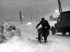 De weg van Velsen naar Amsterdam tijdens de winter van '62-'63. De stuifsneeuwstorm zorgt ervoor dat auto's niet harder dan 30 km/u kunnen rijden, de bromfietsers moeten zelfs lopen, 16 januari 1963.