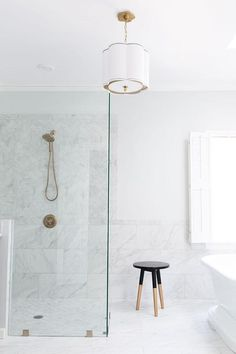Exquisite bathroom features a white scalloped drum pendant with black trim, Hudson Valley Lighting Sweeny Chandelier, illuminating a seamless glass shower filled with gray and white marble like porcelain tiles lined with a gold shower kit Gold Stool, Black Stool, Gold Shower, Glass Shower, Shower Walls, Shower Doors, White Bathroom, Master Bathroom, Family Bathroom