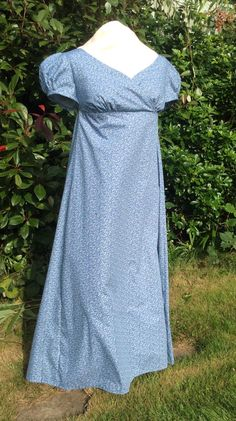 This listing is for a charming Regency day dress made from a historical reproduction printed cotton in Copenhagen blue and white with tiny scrolling leaves and vines. The gown is cut in a classic regency style with flattering wrap over slightly sweetheart neckline with short puffed sleeves. The bodice fastens with handmade fabric covered buttons and is cotton lined. The full length skirt with gathering focused toward the back waist dips slightly longer at the back hem a common feature of…