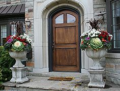 Two large cast planters elevated on plinths, filled with fall mums, ornamental kale, dark red flowering grass.