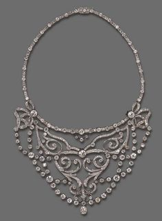 AN ELEGANT BELLE EPOQUE DIAMOND NECKLACE  The central articulated bib, designed as an openwork old mine and old European-cut diamond scrolled plaque, suspending intersecting diamond collet swags, with knife-edge spacers, joined by old mine and old European-cut diamond ribbon bow motifs to the flexible backchain of rose-cut diamond links, enhanced by diamond collet spacers, mounted in platinum, circa 1905