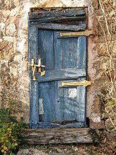 Une très vieille porte peinte en bleu; les planches sont plus ou moins disjointes; les parties métalliques ont été peintes en jaune. // A very old door painted blue; the boards are more or less disjoint(?); the metal parts are painted yellow.