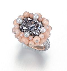 A Colored Diamond, Diamond, Coral and Cultured Pearl Ring, by Taffin. Set with a cushion-shaped fancy violet-grey diamond weighing approximately 5.64 carats (Christie's).