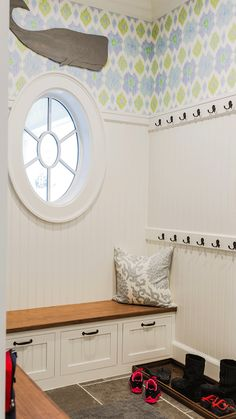 Cottage mudroom boasts blue and green ikat wallpaper on upper walls and beadboard trim on lower ...
