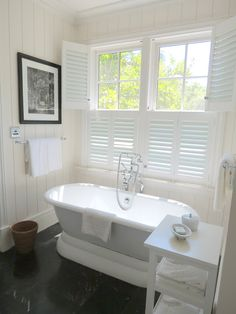 This amazing soaking tub looks simply divine with these white plantation shutters, adding simplicity and privacy
