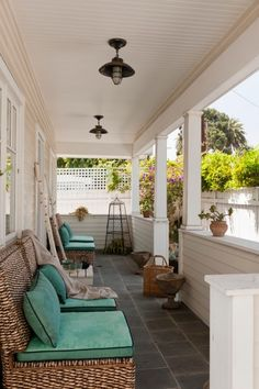 Fuss-Free Venice Beach Bungalow: A seating area greets you with furniture made of banana leaves from Indonesia and plush turquoise cushions. A porch came with the original home, but Tana had it rebuilt, adding more structural support, Pennsylvania Bluestone tiles and pendant lights.