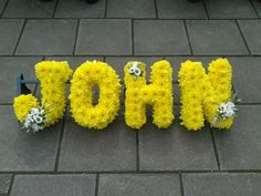 Yellow based letters with yellow ribbon edge & 3 white flower sprays Flower Letters, Flower Names, Funeral Floral Arrangements, Flower Arrangements, Wreaths For Funerals, Florist London, Funeral Tributes, Sympathy Flowers, Same Day Flower Delivery