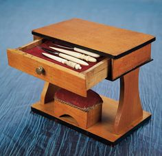 GERMAN WOODEN SEWING NECESSAIRE IN THE SHAPE OF MINIATURE DESK  The maple wood desk with ebony black edging has single drawer that opens to fitted interior with a set of bone-handled sewing tools,and a foot-stool shaped pincushion below with original red velvet cover.  Germany,circa 1885.